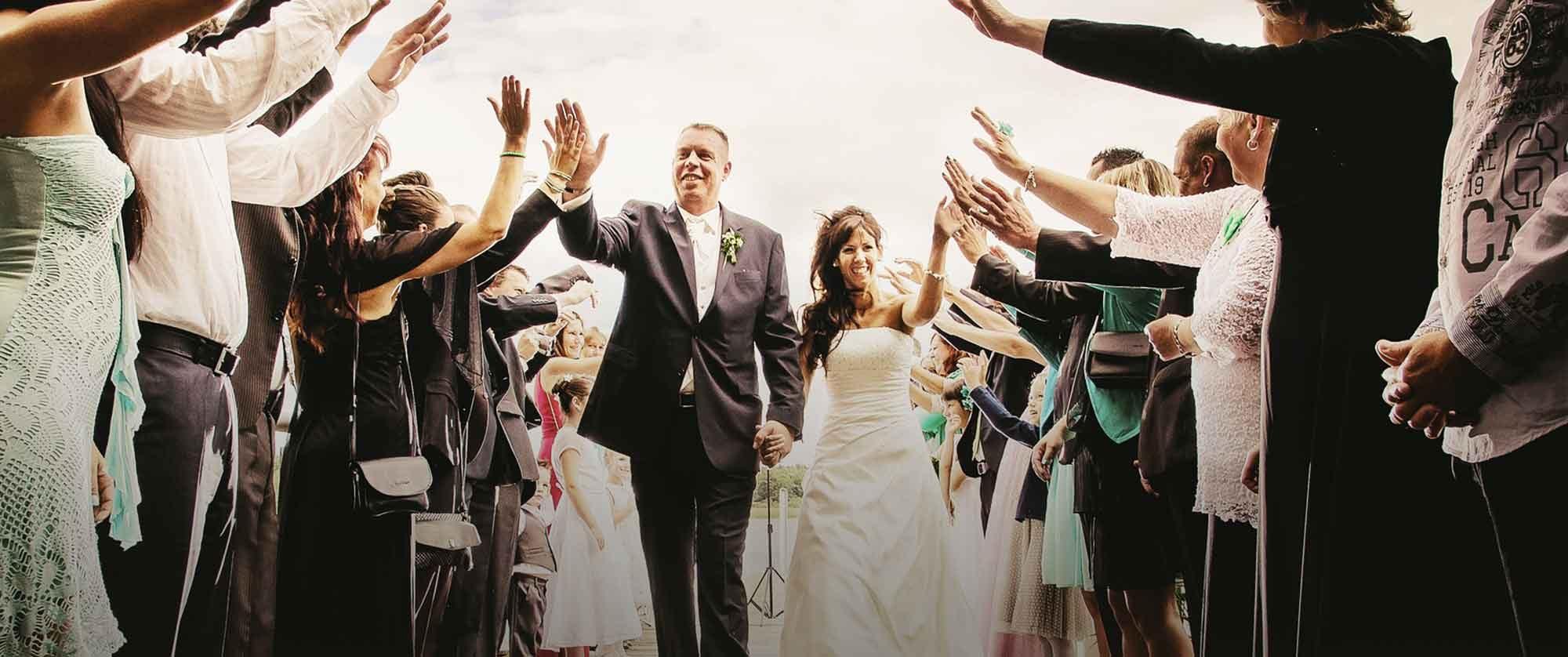 Gäste klatschen mit Brautpaar ein